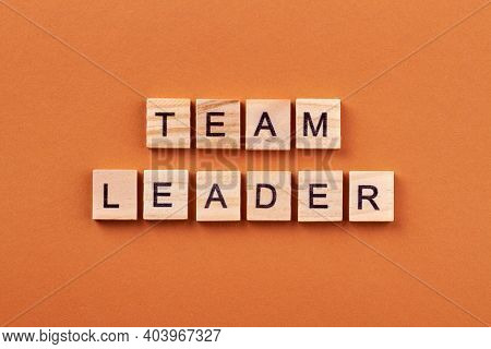 Corporate Concept Of Leadership. Team Leader Text On Wooden Cubes Isolated On Orange Background.
