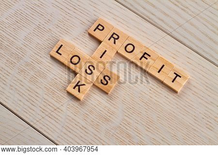 Profit Loss And Risk. Financial Terms For Business. Wooden Blocks With Letters On The Wooden Desk.