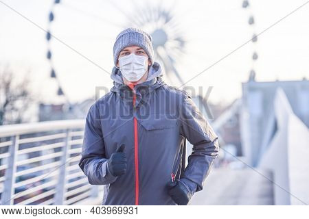 Adult man jogging in the city in masks during lockdown