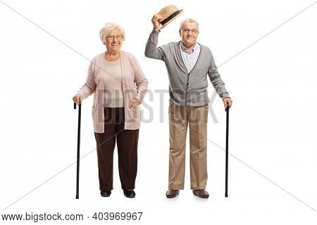 Elderly gentleman greeting with hat and standing with an elderly woman isolated on white background