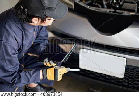 Asian Auto Mechanic Holding Digital Tablet Checking Car Engine And License Plate In Auto Service Gar
