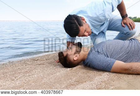 Passerby Checking For Breathing Of Unconscious Young Man Near Sea