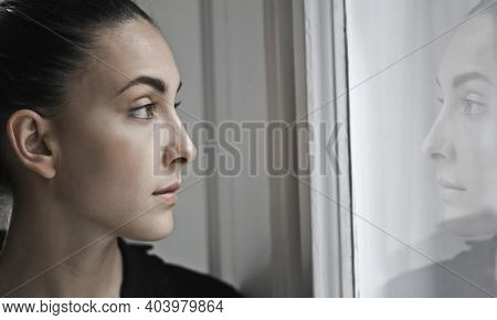 young woman looks out the window