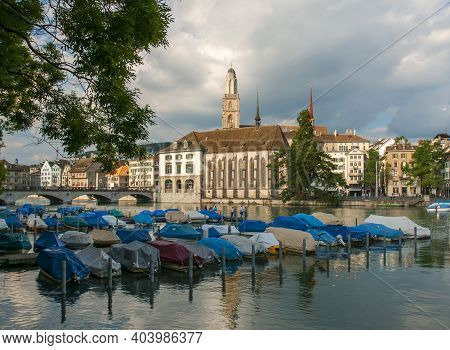 View Of Moored Boats On Limmat River And Grossmunster Church, Townhall And Old City Center On Backgr
