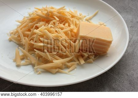 Grated Cheese And A Piece Of Cheese On A Plate. Overhead View. Close-up
