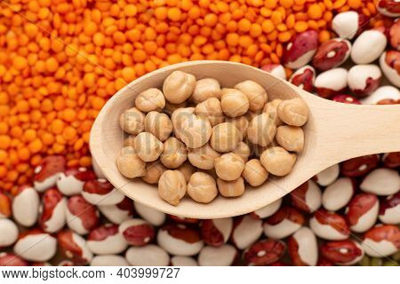 Uncooked Dried Chickpeas In Wooden Spoon Close Up. Heap Of Legume Chickpea Background