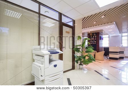 Light corridor near reception in business company with sofas and chairs.