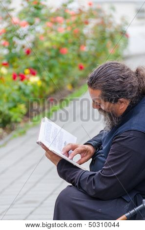 POCHAYIV, UKRAINE - AUGUST 14: Unidentified orthodox priest reading a book in Holy Dormition Pochayiv Lavra, Pochayiv, Ukraine on August 14, 2013
