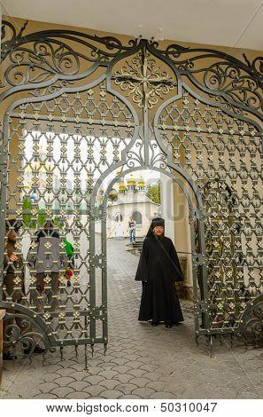 POCHAYIV, UKRAINE - AUGUST 14: Unidentified orthodox priest in entrance to Holy Dormition Pochayiv Lavra, Pochayiv, Ukraine on August 14, 2013