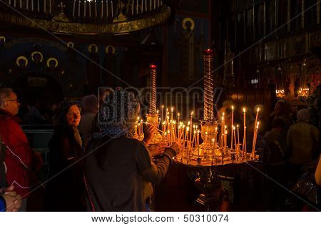 POCHAYIV, UKRAINE - AUGUST 14: Unidentified orthodox believers light candles in Holy Dormition Pochayiv Lavra, Pochayiv, Ukraine on August 14, 2013