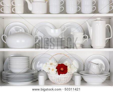 Closeup of white plates and dinnerware in a cupboard. A basket of white and red roses is centered on the bottom shelf. Items include, plates, coffee cups, saucers, soup tureen, tea pot, and gray boats