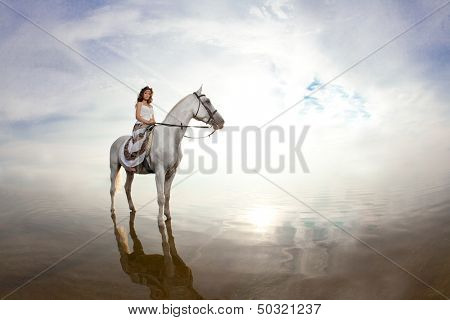 Beautiful woman on a horse. Horseback rider, woman riding horse on beach poster