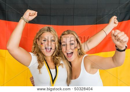 Portrait of successful young sportswomen shouting while standing against German flag