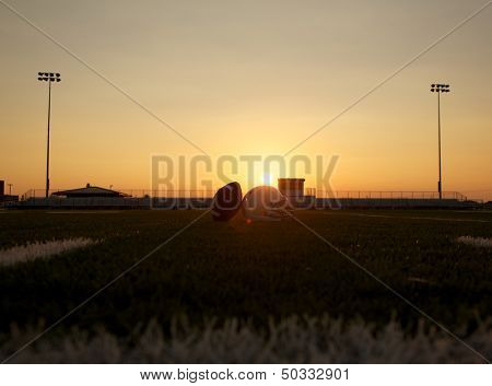 American Football and Helmet on the Field at Sunset with Stands Beyond