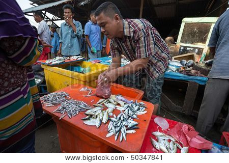 PADANG - AUGUST 25: A fishmonger attends to a customer in a stall at a village market in Padang, West Sumatera, Indonesia on August 25, 2013. Resources from the sea is a major revenue earner.