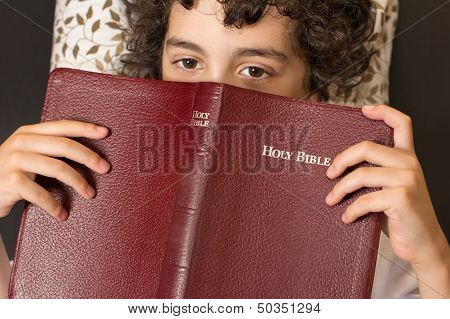 Child Taking a Break from Reading the Bible