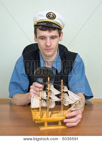 Man With A Magnifier And Model Of A Sailing Vessel