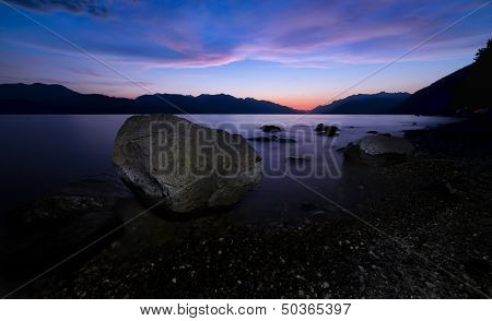 Large Rock Along Lake Shore At Night