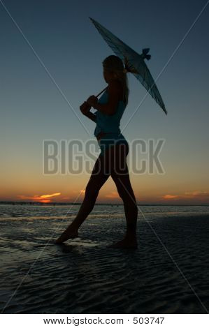 Young Woman Watches Sunset Under A Parasol