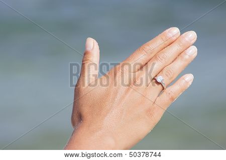 Woman Hand With Engagement Ring On The Beach