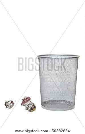 Crumpled papers next to empty wastebasket over white background