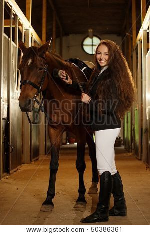Beautiful girl with her horse in a stall  poster