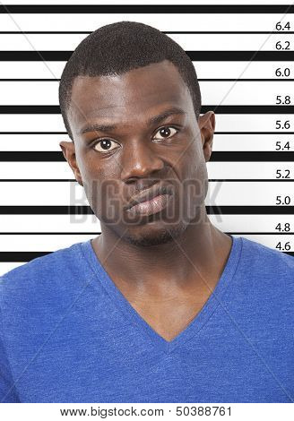 Portrait of angry young African American man against height chart