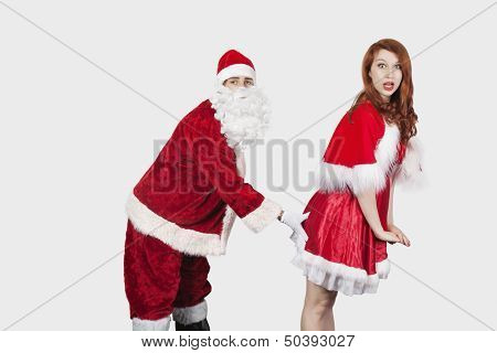 Portrait of Santa touching Mrs. Santa inappropriately against gray background poster