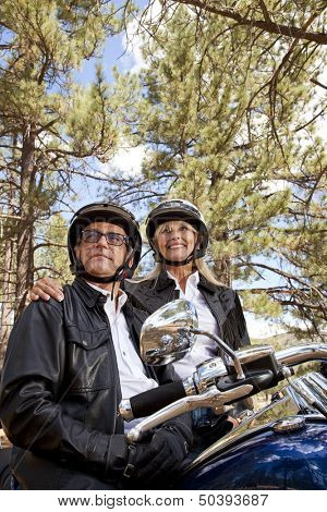 Senior couple wearing helmets stand next to motorcycle
