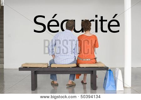 """Rear view of couple reading French text """"s_curit_"""" (security) and contemplating about security"""