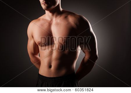 Muscular young sexy nude man on studio poster