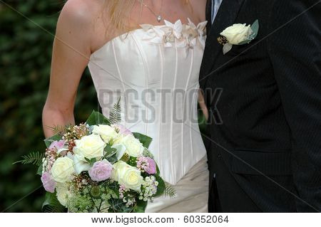 Wedding couple standing together holding flowers.