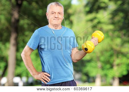 Senior man exercising with weight in a park poster
