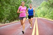 Athletes running - sport couple jogging in summer. Runners jogging in summer on road. Joggers training for marathon run. Fit male and female athletes in their 20s. Asian woman, Caucasian man. poster
