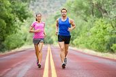 Fitness sport couple running jogging outside on road beautiful nature landscape. Runners training together for marathon run. Asian female sports woman and fit male fitness man in full body length. poster