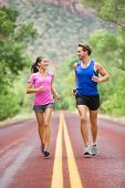Two people jogging for fitness running on road outside in beautiful landscape nature. Woman and man sports athletes training for marathon. Couple together, Asian woman, Caucasian man, poster