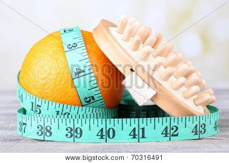Fresh orange, tapeline and a brush on grey wooden table