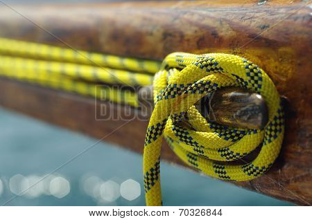 Closeup Of Old Vintage Snatch Cleat With Yellow Line On Wooden Yacht, Tool For Keeping Ropes Tighten