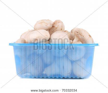 Champignon mushrooms on plastic box.