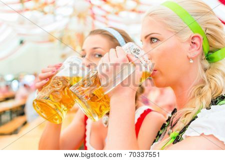 Women drinking Bavarian beer in tent on Oktoberfest or dult wearing dirndl