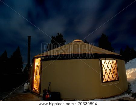a yurt in the snowy mountains at night