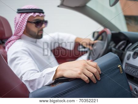 Arabic young businessman driving car and holding briefcase