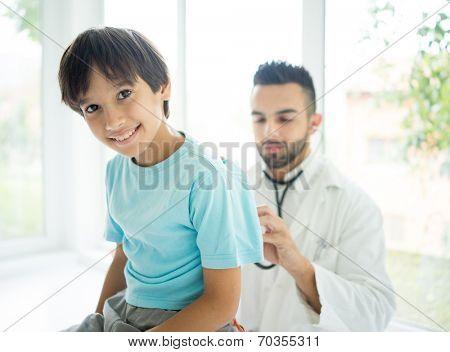 Doctor examining a school boy at hospital