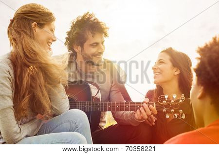 Happy group of friends enjoying the summer outdoor playing guitar and singing together poster