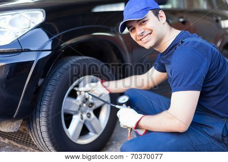 Smiling mechanic inflating a tire