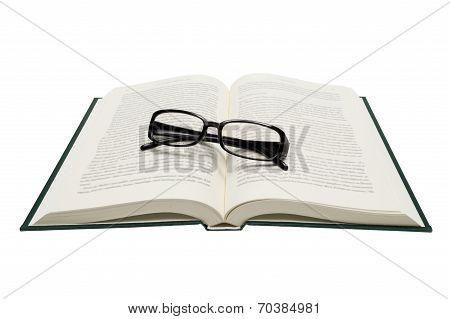 Folded Eyeglasses On Opened Book