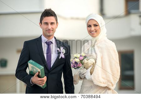 Happy islamic couple posing in front of mosque