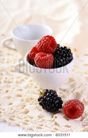 Raspberries and blueberries in cups