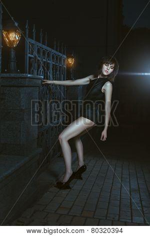 Girl At Night Knocking On Gate.