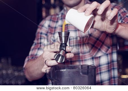 Bartender is pouring mango juice in jigger, toned image